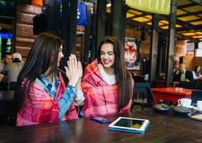 Two young and beautiful girls having fun in cafe Royalty Free Stock Photos