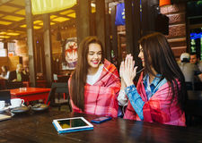 Two young and beautiful girls having fun in cafe Royalty Free Stock Image