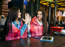 Two young and beautiful girls having fun in cafe Stock Photography