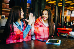 Two young and beautiful girls having fun in cafe Stock Images