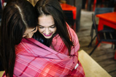 Two young and beautiful girls having fun in cafe Royalty Free Stock Photography