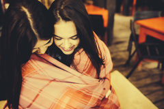 Two young and beautiful girls having fun in cafe Royalty Free Stock Images