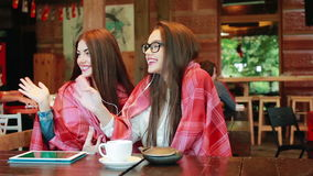 Two young and beautiful girls having fun in cafe. Two beautiful girls waved to the other side of the camera stock footage