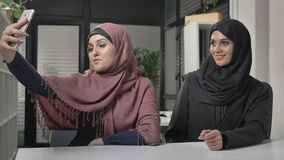 Two young beautiful girls in hijabs are sitting in the office and making selfies. Arab women in the office. 60 fps. 4k stock video