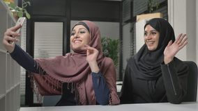 Two young beautiful girls in hijabs are sitting in the office and making selfies. Arab women in the office. Showing. Hello sign in video chat 60 fps 4k stock video