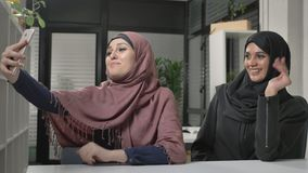 Two young beautiful girls in hijabs are sitting in the office and making selfies. Arab women in the office. Showing. Hello sign in video chat. Waving their stock footage