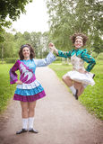 Two young beautiful girls in irish dance dress dancing outdoor Royalty Free Stock Images