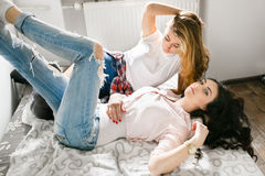 Two young beautiful girls laughing and posing in the bedroom sit Stock Images