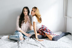 Two young beautiful girls laughing and posing in the bedroom sit Royalty Free Stock Photo