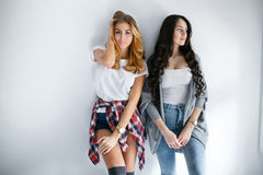 Two young beautiful girls laughing and posing on wall background Stock Image