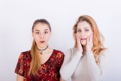 Two young beautiful girls look very surprised. After hearing the news Stock Images