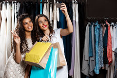 Two young beautiful girls making selfie in shopping mall. Two young beautiful girls making selfie, holding purchases, smiling in shopping mall Stock Images