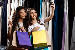 Two young beautiful girls making selfie in shopping mall. Two young beautiful girls making selfie, holding purchases, smiling in shopping mall Royalty Free Stock Images
