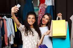Two young beautiful girls making selfie in shopping mall. Two young beautiful girls making selfie, holding purchases, smiling in shopping mall Royalty Free Stock Image