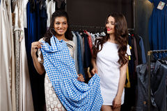 Two young beautiful girls making shopping in mall. Two young beautiful girls in dresses making shopping, smiling in mall Royalty Free Stock Images