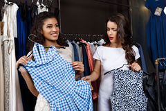 Two young beautiful girls making shopping in mall. Two young beautiful girls in dresses making shopping, smiling in mall Royalty Free Stock Photos