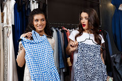 Two young beautiful girls making shopping in mall. Two young beautiful girls in dresses making shopping, smiling in mall Stock Images