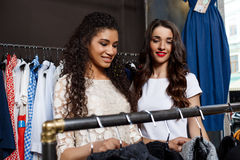Two young beautiful girls making shopping in mall. Two young beautiful girls in dresses making shopping, smiling in mall Stock Photo