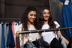 Two young beautiful girls making shopping in mall. Two young beautiful girls in dresses making shopping, smiling in mall Royalty Free Stock Photo