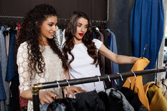 Two young beautiful girls making shopping in mall. Two young beautiful girls in dresses making shopping, smiling in mall Royalty Free Stock Image