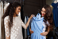 Two young beautiful girls making shopping in mall. Two young beautiful girls in dresses making shopping, smiling in mall Royalty Free Stock Photography