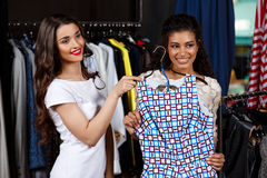 Two young beautiful girls making shopping in mall. Two young beautiful girls in dresses making shopping, smiling in mall Stock Photography