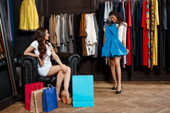 Two young beautiful girls making shopping in mall. Two young beautiful girls making shopping, smiling in mall Royalty Free Stock Image
