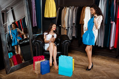 Two young beautiful girls making shopping in mall. Two young beautiful girls making shopping, smiling in mall Royalty Free Stock Photo