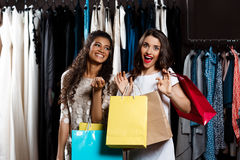 Two young beautiful girls making shopping in mall. Two young beautiful girls making shopping, smiling, holding purchases in mall Royalty Free Stock Image