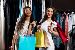 Two young beautiful girls making shopping in mall. Two young beautiful girls making shopping, smiling, holding purchases in mall Stock Photography