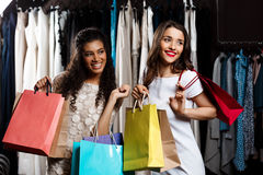 Two young beautiful girls making shopping in mall. Two young beautiful girls making shopping, smiling, holding purchases in mall Stock Photos