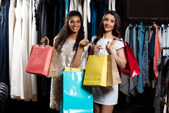 Two young beautiful girls making shopping in mall. Two young beautiful girls making shopping, smiling, holding purchases in mall Stock Image