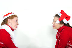 Two young beautiful girls in New Year's caps. Put out the tongue each other Royalty Free Stock Photography