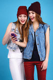 Two young beautiful girls read messages on your mobile phone Royalty Free Stock Image