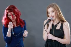 Two young beautiful girls singing Stock Images
