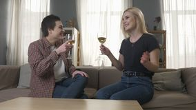 Two young, beautiful girls are sitting on the couch, raise glasses with wine and clinking, lesbians, LGBT, blonde. Two young, beautiful girls are sitting on the stock footage