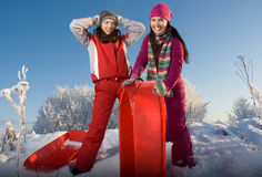 Two young beautiful girls with sledges Stock Image