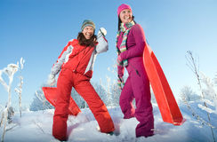 Two young beautiful girls with sledges Royalty Free Stock Images