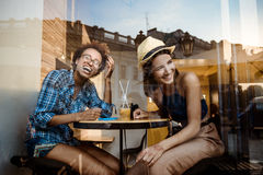 Two young beautiful girls smiling, laughing, resting in cafe. Shot from outside. Stock Photography