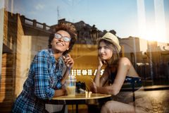 Two young beautiful girls smiling, speaking, resting in cafe. Shot from outside. Stock Photography