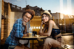 Two young beautiful girls smiling, speaking, resting in cafe. Shot from outside. Stock Photos