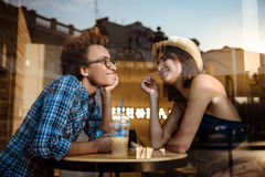 Two young beautiful girls smiling, speaking, resting in cafe. Shot from outside. Royalty Free Stock Image
