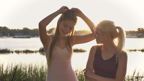 Two young beautiful girls standing on beach looking at each other then in camera, smiling, lens flare, river and nature. Background stock video footage