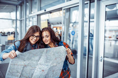Two young beautiful girls are studying and looking at the map.Ar Royalty Free Stock Photos
