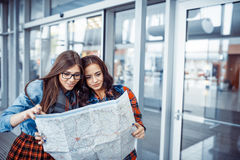 Two young beautiful girls are studying and looking at the map.Ar Stock Image