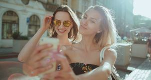 Two young beautiful girls taking selfie on a city street. Young girlfriends enjoying sunny day and using phone, outdoors stock video footage
