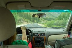 Two young beautiful girls traveling by car in the mountains of the Altai are driving by serpentine road. Woman look in to the stock image