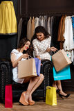 Two young beautiful girls viewing buyings in shopping mall. Royalty Free Stock Images