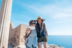 Two young beautiful happy woman female travel girlfriends doing stock photo