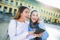 Two young beautiful happy women looking something on digital tablet. Two young beautiful happy women  smiling ,talking and looking something on digital tablet Royalty Free Stock Photo